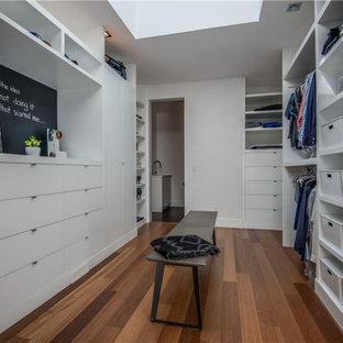Imagen de armario vestidor unisex, actual, grande, con armarios con paneles lisos, puertas de armario blancas, suelo de madera en tonos medios y suelo marrón