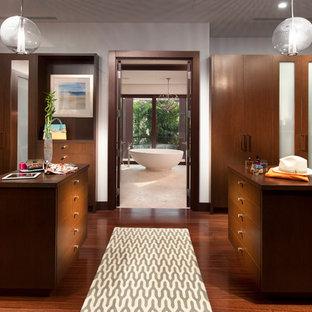 Idées déco pour un dressing room contemporain neutre avec un placard à porte plane et des portes de placard en bois sombre.