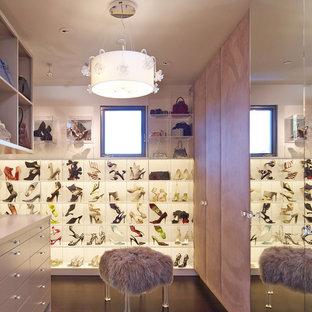 Ejemplo de armario vestidor de mujer, actual, extra grande, con armarios abiertos, suelo de madera oscura, puertas de armario blancas y suelo marrón