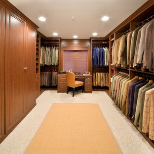 This is an example of an expansive contemporary men's walk-in wardrobe in Chicago with raised-panel cabinets, medium wood cabinets and carpet.