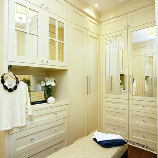 Example of a trendy women's dark wood floor dressing room design in Other with beige cabinets and shaker cabinets