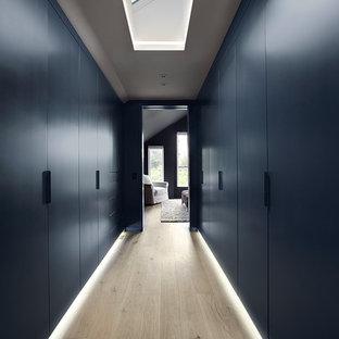 Inspiration för ett stort funkis walk-in-closet, med släta luckor, blå skåp och ljust trägolv