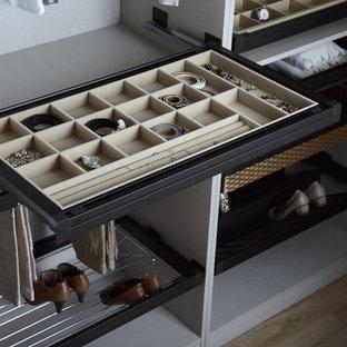 Foto de armario vestidor unisex, contemporáneo, de tamaño medio, con armarios abiertos, puertas de armario grises, suelo de madera clara y suelo beige