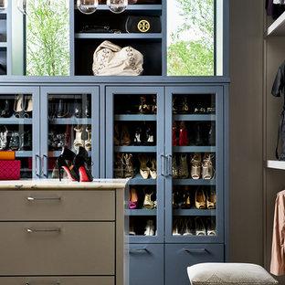 Exemple d'un dressing tendance pour une femme avec un placard à porte vitrée, des portes de placard bleues et un sol en bois foncé.