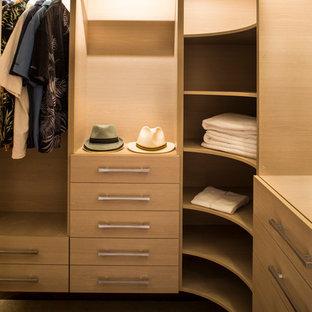 Immagine di una piccola cabina armadio unisex contemporanea con ante lisce, ante in legno chiaro e moquette