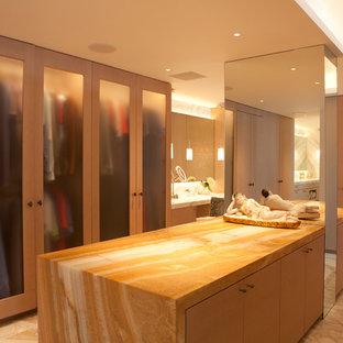 Ejemplo de vestidor unisex, actual, extra grande, con armarios con paneles lisos, puertas de armario de madera clara, suelo de mármol y suelo beige