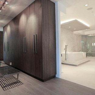 Foto de vestidor unisex, actual, grande, con armarios con paneles lisos, puertas de armario de madera oscura, suelo de madera clara y suelo gris
