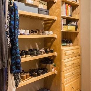 Idee per una grande cabina armadio per donna design con ante a filo, ante in legno bruno e pavimento in pietra calcarea