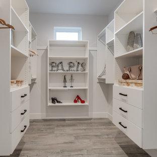 Diseño de armario vestidor unisex, contemporáneo, de tamaño medio, con armarios con paneles lisos, puertas de armario blancas, suelo laminado y suelo gris