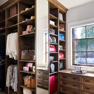 Réalisation d'un grand dressing room champêtre neutre avec un placard sans porte, des portes de placard en bois brun, moquette et un sol gris.