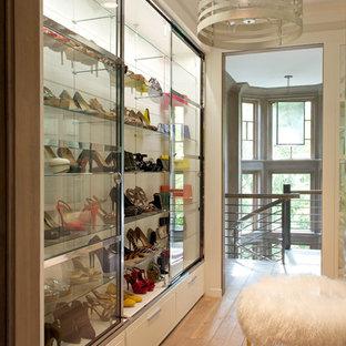 Idée de décoration pour un dressing room victorien pour une femme avec un placard à porte vitrée et un sol en bois clair.