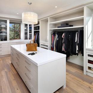 Imagen de vestidor de mujer, contemporáneo, con puertas de armario blancas, suelo de madera clara y armarios con paneles lisos
