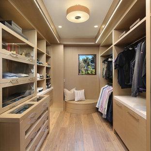 サンフランシスコの巨大な男性用コンテンポラリースタイルのおしゃれなフィッティングルーム (淡色無垢フローリング、ガラス扉のキャビネット、ベージュのキャビネット、ベージュの床) の写真