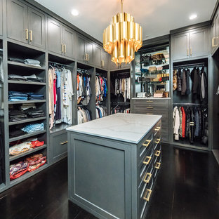 Large transitional gender-neutral walk-in wardrobe in Dallas with grey cabinets, dark hardwood floors, brown floor and shaker cabinets.