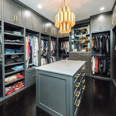Inspiration for a large transitional gender-neutral dark wood floor and brown floor walk-in closet remodel in Dallas with gray cabinets and shaker cabinets