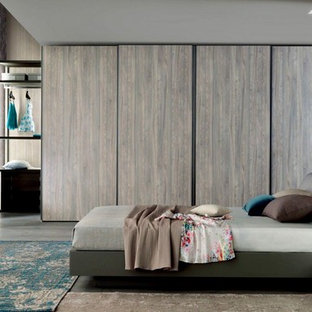 This is an example of a large contemporary gender-neutral built-in wardrobe in Miami with flat-panel cabinets, light wood cabinets, concrete floors and grey floor.