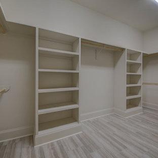 Modelo de armario vestidor unisex, clásico renovado, grande, con armarios abiertos, puertas de armario beige y suelo de baldosas de porcelana