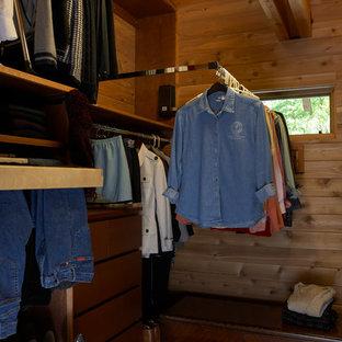 Foto de armario vestidor unisex, clásico renovado, de tamaño medio, con armarios con paneles lisos, puertas de armario de madera oscura y suelo de madera oscura