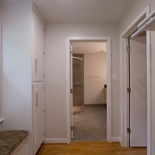 Foto de vestidor unisex, actual, de tamaño medio, con armarios con paneles lisos, puertas de armario blancas, suelo de madera en tonos medios y suelo naranja