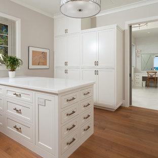 Ejemplo de vestidor unisex, costero, con armarios estilo shaker, puertas de armario blancas y suelo de madera clara