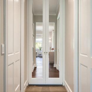 Ejemplo de armario vestidor unisex, clásico, grande, con puertas de armario blancas, suelo de madera en tonos medios y suelo marrón