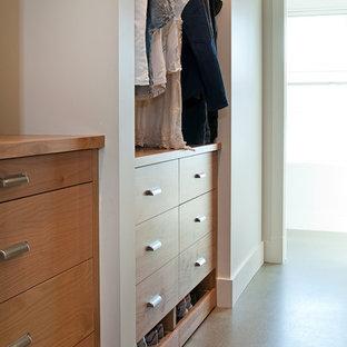 Foto de armario vestidor unisex, clásico renovado, de tamaño medio, con armarios con paneles lisos, puertas de armario de madera oscura y suelo de cemento