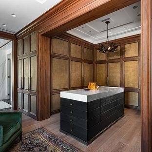 Diseño de vestidor de hombre, clásico renovado, grande, con armarios con paneles empotrados, suelo marrón, puertas de armario de madera oscura y suelo de madera clara