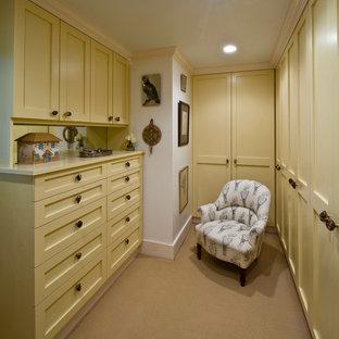 Immagine di un'ampia cabina armadio per donna tradizionale con ante in stile shaker, ante gialle, moquette e pavimento beige
