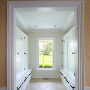 Example of a large beach style gender-neutral limestone floor walk-in closet design in New York with recessed-panel cabinets and white cabinets