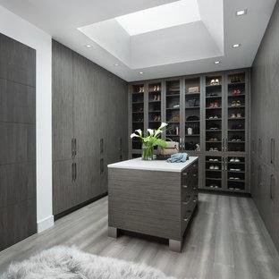 Modernes Ankleidezimmer mit Ankleidebereich, flächenbündigen Schrankfronten, dunklen Holzschränken und braunem Boden in Detroit