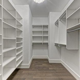 ニューヨークの中くらいの男女兼用トランジショナルスタイルのおしゃれなウォークインクローゼット (フラットパネル扉のキャビネット、白いキャビネット、塗装フローリング、茶色い床) の写真