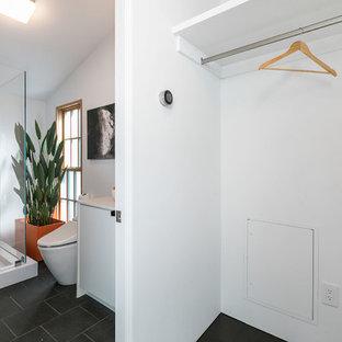 Imagen de armario unisex, ecléctico, con puertas de armario blancas, suelo de pizarra, suelo negro y armarios con paneles lisos
