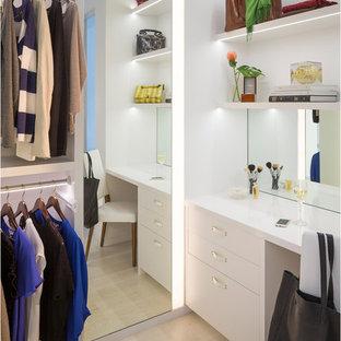 Cette image montre un grand dressing design pour une femme avec un placard à porte plane, des portes de placard blanches et un sol en bois clair.