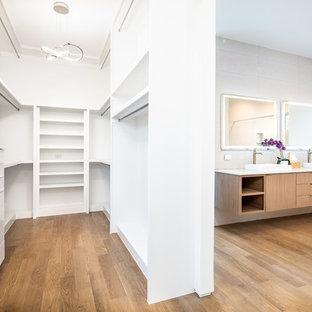 Foto di una cabina armadio unisex minimalista di medie dimensioni con nessun'anta, ante bianche, pavimento in legno massello medio e pavimento marrone