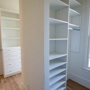 Modelo de armario vestidor unisex, de estilo de casa de campo, grande, con armarios abiertos, puertas de armario blancas, suelo de madera clara y suelo marrón