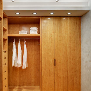 This is an example of a small contemporary gender-neutral walk-in wardrobe in New York with open cabinets, light wood cabinets and bamboo floors.