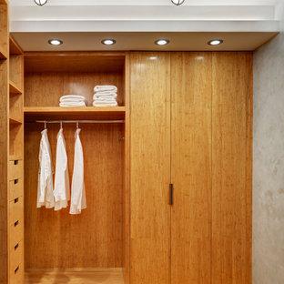 Réalisation d'un petit dressing design neutre avec un placard sans porte, des portes de placard en bois clair et un sol en bambou.