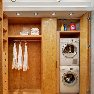 Diseño de armario vestidor unisex, contemporáneo, pequeño, con armarios abiertos, puertas de armario de madera clara y suelo de bambú