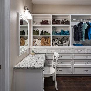 Réalisation d'un grand dressing room craftsman neutre avec un placard avec porte à panneau encastré, des portes de placard blanches, un sol en bois foncé et un sol marron.