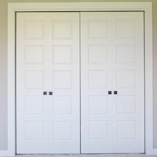 Ejemplo de armario unisex, de estilo americano, con puertas de armario blancas, moqueta y suelo gris