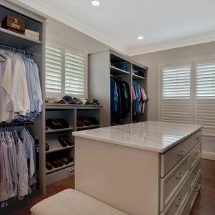 Modelo de armario vestidor unisex, de estilo americano, grande, con armarios con paneles empotrados, puertas de armario grises y suelo de madera en tonos medios