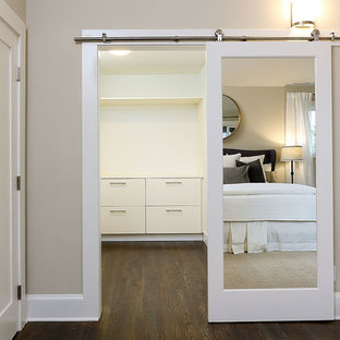 Idéer för att renovera ett mellanstort vintage walk-in-closet för könsneutrala, med släta luckor, vita skåp, mörkt trägolv och brunt golv