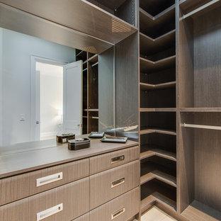 Diseño de armario vestidor unisex, contemporáneo, de tamaño medio, con armarios con paneles lisos, puertas de armario marrones, suelo de madera clara y suelo amarillo