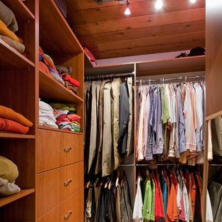 Photo of a mid-sized midcentury gender-neutral walk-in wardrobe in Vancouver with flat-panel cabinets, medium wood cabinets and carpet.