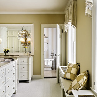 This is an example of a classic dressing room in New York with carpet and white cabinets.