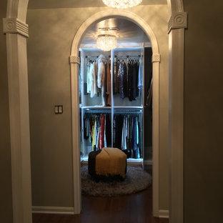 ワシントンD.C.の中サイズの男女兼用ミッドセンチュリースタイルのおしゃれなウォークインクローゼット (レイズドパネル扉のキャビネット、白いキャビネット、無垢フローリング) の写真