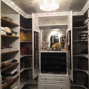 This is an example of a mid-sized midcentury gender-neutral walk-in wardrobe in DC Metro with raised-panel cabinets, white cabinets and medium hardwood floors.
