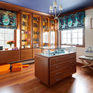 Example of a mid-sized transitional women's medium tone wood floor and orange floor dressing room design in New York with glass-front cabinets and medium tone wood cabinets