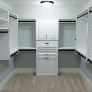 This is an example of a mid-sized traditional women's walk-in wardrobe in Atlanta with raised-panel cabinets, white cabinets and carpet.