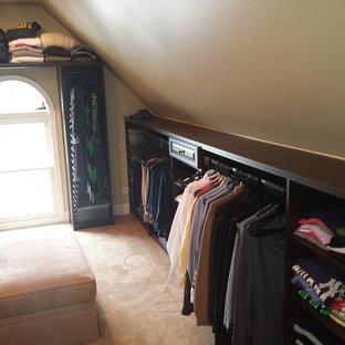 Стильный дизайн: гардеробная комната среднего размера, унисекс в классическом стиле с фасадами с выступающей филенкой, темными деревянными фасадами и ковровым покрытием - последний тренд